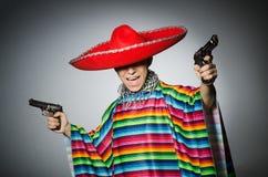 Man i hållande handeldvapen för livlig mexikansk poncho Fotografering för Bildbyråer