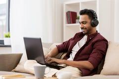 Man i hörlurar med bärbara datorn som lyssnar till musik fotografering för bildbyråer