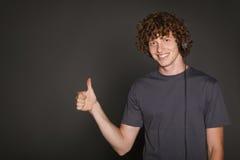 Man i hörlurar som gör en gest upp tummen Fotografering för Bildbyråer