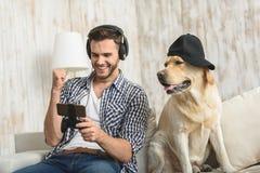 Man i hörlurar som sitter med hans kalla hund royaltyfri fotografi