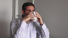 Man i hans forties (40-tal) som dricker en varm drink lager videofilmer