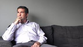 Man i hans forties (40-tal) som sitter på en soffarubbning lager videofilmer