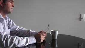 Man i hans forties (40-tal) som sitter på en tabellrubbning arkivfilmer