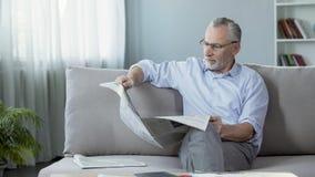 Man i hans 60-tal som sitter på soffan och den läs- tidningen, morgonritual, press Royaltyfri Fotografi