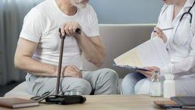 Man i hans 50-tal som sitter på soffan och talar med doktorn, sjukvård och sjukdom Arkivbild
