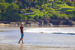 Man i hatt på en strand Royaltyfri Foto