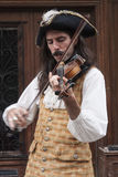 Man i historisk kläder som spelar en fiol Arkivbild