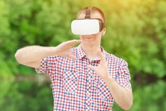 Man i hjälm av virtuell verklighet mot bakgrunden av natur arkivfoton