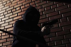 Man i hoodie med vapnet Farlig brottsling royaltyfri foto