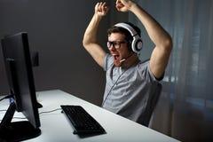 Man i hörlurar med mikrofon som hemma spelar datorvideospelet Royaltyfri Foto