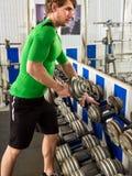 Man i idrottshall med konditionutrustning Idrottshall för mangenomkörarehantel Royaltyfria Bilder