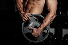 Man i idrottshall Muskulös kroppsbyggaregrabb som gör övningar med skivstången Stark person med den spända starka manliga handen  Arkivfoton