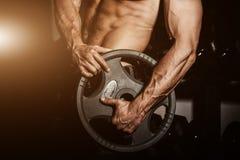 Man i idrottshall Muskulös kroppsbyggaregrabb som gör övningar med skivstången Stark person med den spända starka manliga handen  Arkivbilder