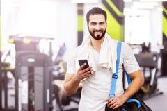 Man i idrottshallen med telefonen royaltyfri fotografi