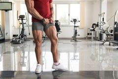 Man i idrottshallen som visar hans välutbildade ben arkivbild