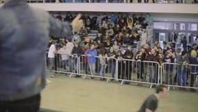 Man i inkört främre folk för hatt i skatepark som gör vågen vid händer på tribun konkurrens värds arkivfilmer