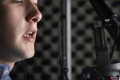 Man i inspelningstudio som talar in i mikrofonen Royaltyfri Foto