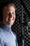 Man i inspelningstudio som talar in i mikrofonen Arkivfoto