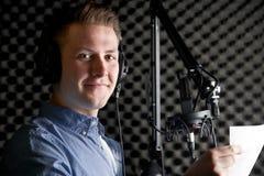 Man i inspelningstudio som talar in i mikrofonen Royaltyfria Bilder