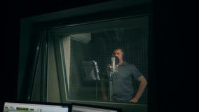 Man i inspelningstudio som talar in i mikrofonen Sikt till och med exponeringsglaset stock video