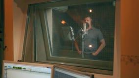 Man i inspelningstudio som talar in i mikrofonen Sikt till och med exponeringsglaset lager videofilmer