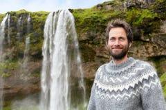 Man i isländsk tröja vid vattenfallet på Island Arkivfoto