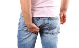 Man i jeans som skrapar handen hans kliande botten royaltyfria bilder