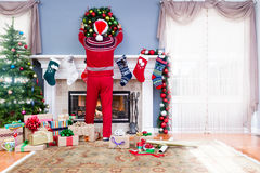 Man i jultomtendräkt som dekorerar för jul Arkivfoton