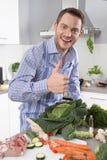 Man i köket med tummen som förbereder upp matställen arkivbilder
