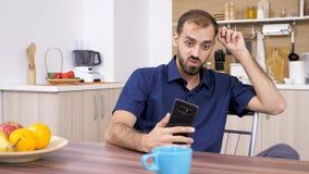 Man i köket som talar med något på telefonen stock video