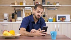 Man i köket som talar med något på telefonen lager videofilmer