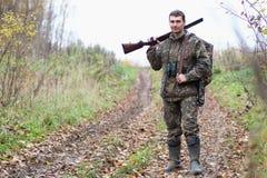 Man i kamouflage och med vapen i ett skogbälte på en vårhun Royaltyfri Foto
