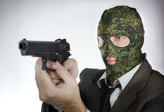 Man i kamouflagemaskering med en pistol Arkivfoton