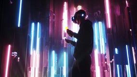 Man i kontrollanter för flyttning för VR-hörlurar med mikrofoninnehav i neonljus lager videofilmer