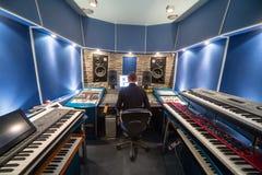 Man i kontrollrum med musikutrustning royaltyfria bilder