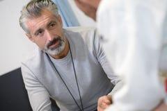 Man i konversation med doktorn royaltyfri foto