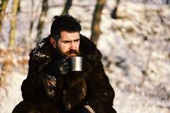 Man i kopp för metall för håll för pälslag Grabb i skog royaltyfria bilder