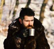 Man i kopp för metall för håll för pälslag Värmedrinkbegrepp royaltyfri foto