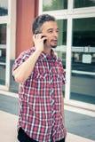 Man i kort muffskjorta som talar på telefonen Arkivbild