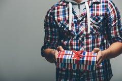 Man i kulöra skjortainnehavgåvor Royaltyfri Foto
