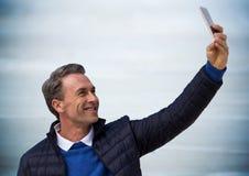 Man i laget som tar selfie mot oskarp blå wood panel Royaltyfri Bild