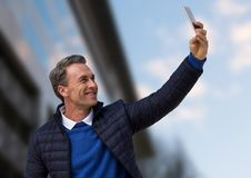 Man i laget som tar selfie mot oskarp byggnad Royaltyfria Bilder