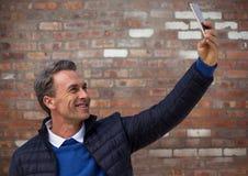 Man i laget som tar selfie mot väggen för röd tegelsten Royaltyfria Foton