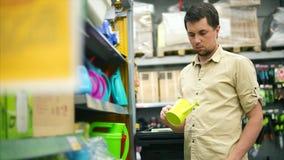 Man i lagret Kunden som tar kortkortet som bevattnar kan och att undra arkivfilmer