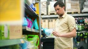 Man i lagret Kunden som tar kortkortet som bevattnar kan och att undra lager videofilmer