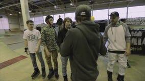 Man i lock med mikrofonrazzianäven med rullskateboradåkare på konkurrens i skatepark cameraman lager videofilmer
