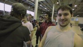 Man i lock med mikrofonrazzianäven med rullskateboradåkare på konkurrens i skatepark värds stock video