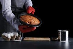 man i m?rk bakgrund f?r r?d potholderinnehavpaj och som isolerar p? svart receptbegrepp med ingredienser p? tabellen arkivfoton