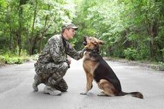 Man i militär likformig med hunden för tysk herde royaltyfria bilder