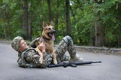 Man i militär likformig med hunden för tysk herde arkivfoto